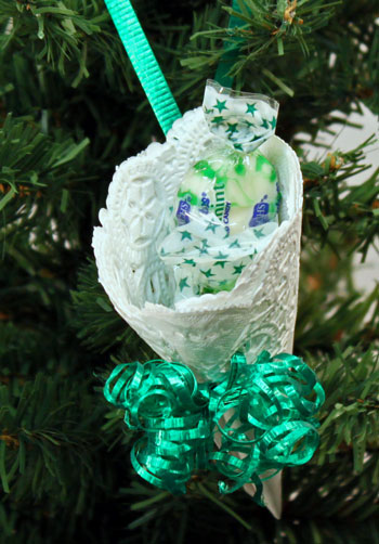 Easy Christmas Crafts Paper Doily Cone Ornament finished with green ribbon hanging on tree