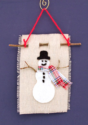 Easy Christmas Crafts Felt and Twig Snowman finished and hanging on a wall