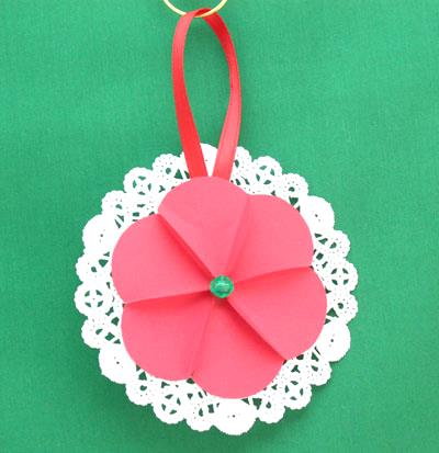 Paper Circles Triangle Doily Ornament in red handing on display